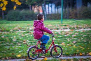 jongetje fiets door een park