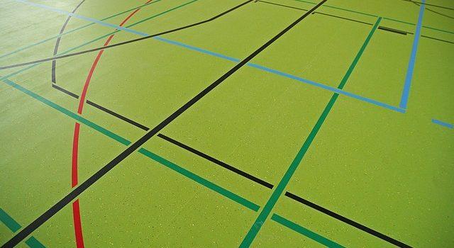 Groene vloer van een sporthal met gekleurde lijnen van verschillende sporten